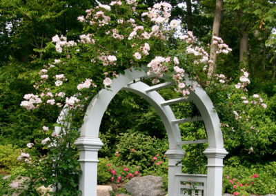 Decorative arbor with picket fence and bluestone walkway.