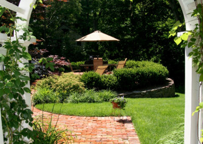 Arbor with running bond brick walkway and stone wall.