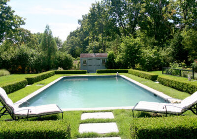 Formal boxwood hedge surrounding a gunite pool.