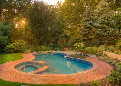 Gunite pool and spa with a brick patio.
