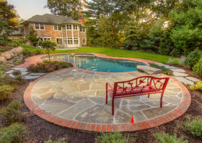 Secluded gunite pool and spa surrounded by a bluestone patio with brick coping.