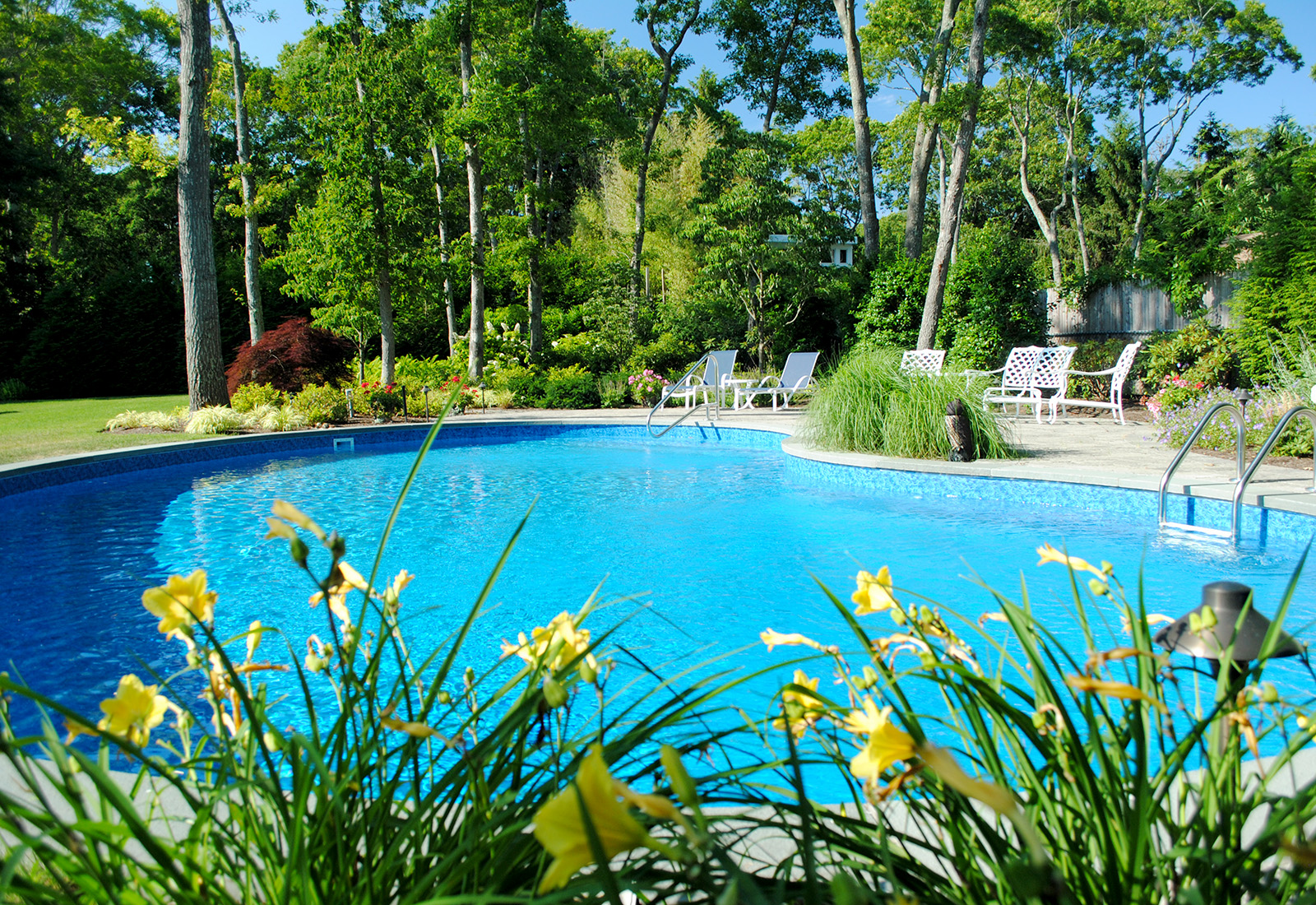 Enjoy the outdoors with a pool surrounded by flowering perennials.