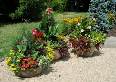 Mixed color pots on a bed of gravel.