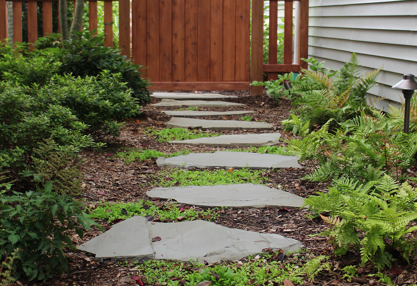 Custom wood gate and a natural stone garden path.